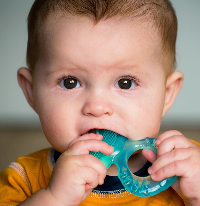 Child in need of pulp therapy chewing on teething ring