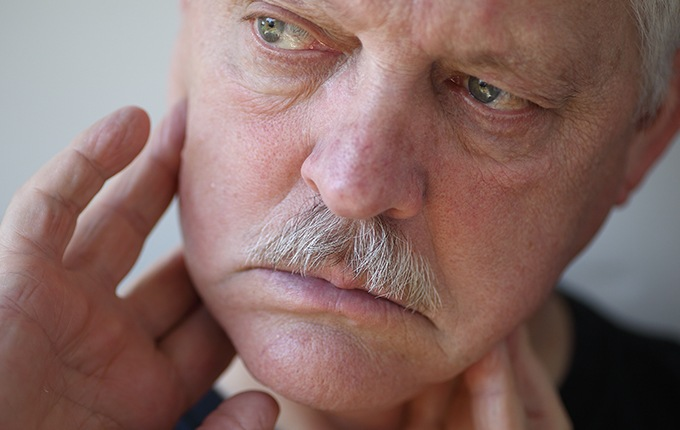 Man with toothache holding jaw