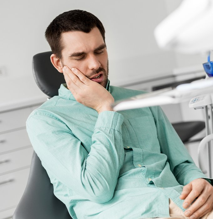 Man holding jaw during emergency dentistry