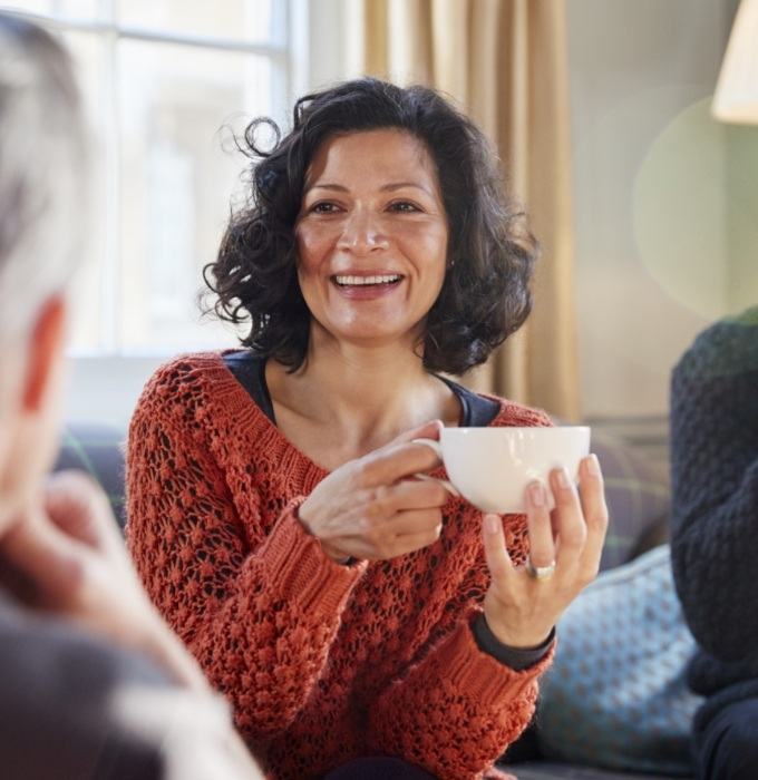 Smiling woman holding coffee cup after dental implant supported tooth replacement